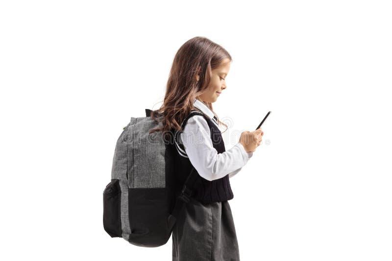 Mała uczennica używa telefon komórkowego fotografia royalty free