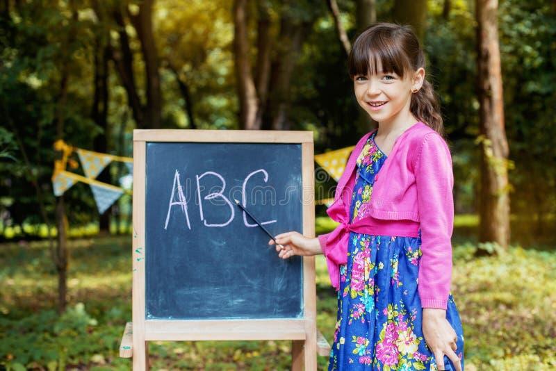 Mała uczennica uczy abecadło blisko blackboard tylna szko?y Pojęcie edukacja, szkoła, dzieciństwo obraz stock