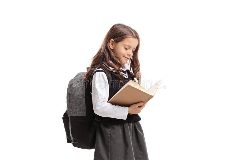 Mała uczennica w jednolitym czytaniu książka zdjęcia stock