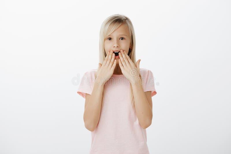 Mała urocza dziewczyna ogląda ciekawą kreskówkę, zadziwiający z czym zdarza się Portret zdziwiony wstrząśnięty śliczny obrazy stock