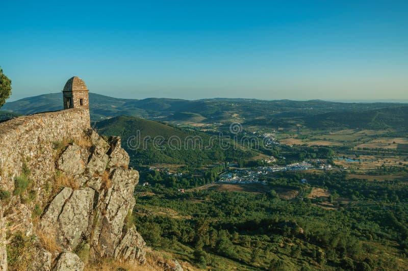 Mała wieża obserwacyjna i kamienna ściana nad falezą z górzystym krajobrazem fotografia stock