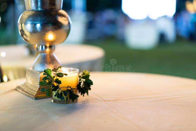 Mała wygodna świeczka na białym okręgu stole z plamy tłem obraz royalty free