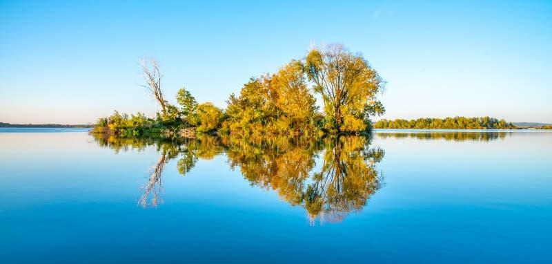 Mała wyspa z gren luksusowych drzewa i jasnego niebieskie niebo odbijających w spokój wodzie Nove Mlyny tama, Moravia, republika  obrazy stock