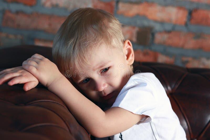 Mała wzburzona chłopiec na kanapie fotografia royalty free