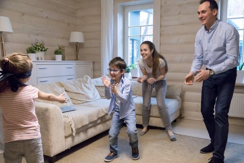 Mała z zasłoniętymi oczami dziewczyna bawić się kryjówkę aport z rodziną - i - fotografia stock