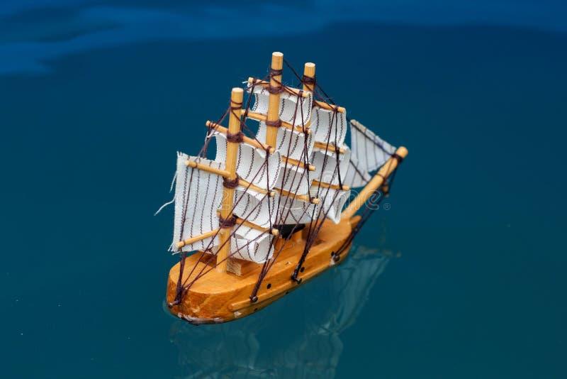 mała zabawkarska łódź w wodzie z dużych fal statku modela żaglówki tła białym drewnianym złotem fotografia stock