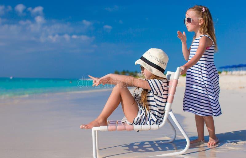 Małe śliczne dziewczyny na bielu wyrzucać na brzeg podczas wakacje obraz stock