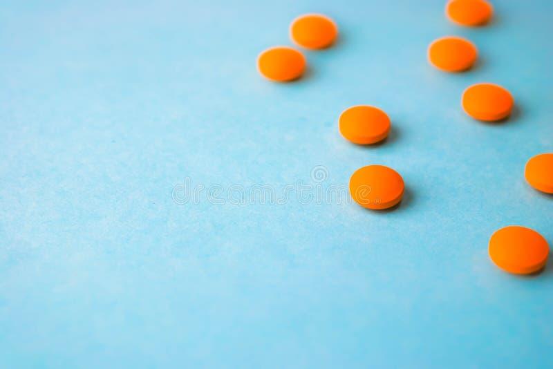 Małe żółte pomarańczowe piękne medyczne pharmaceptic round pigułki, witaminy, leki, antybiotyki na błękitnym tle, tekstura zdjęcie royalty free