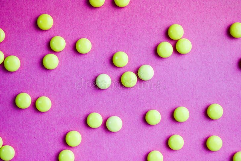 Małe żółte pomarańczowe piękne medyczne pharmaceptic round pigułki, witaminy, leki, antybiotyki na różowym purpurowym tle, tekstu obraz royalty free