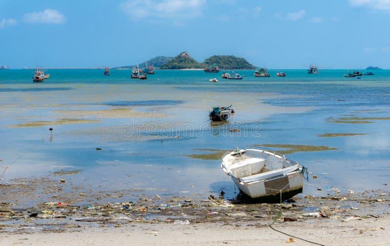 Małe białe fiberglass łodzie rybackie cumuje przy brudną plażą fotografia royalty free