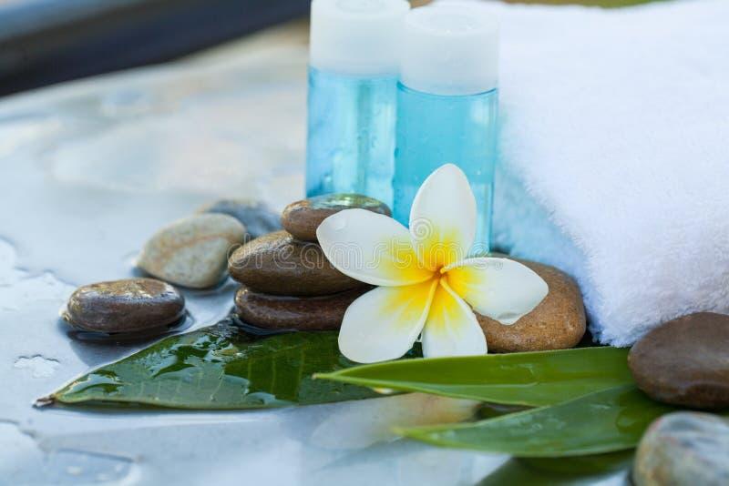 Małe butelki z tropikalnym kwiatem i kamieniami dla masażu traktowania zdjęcia stock