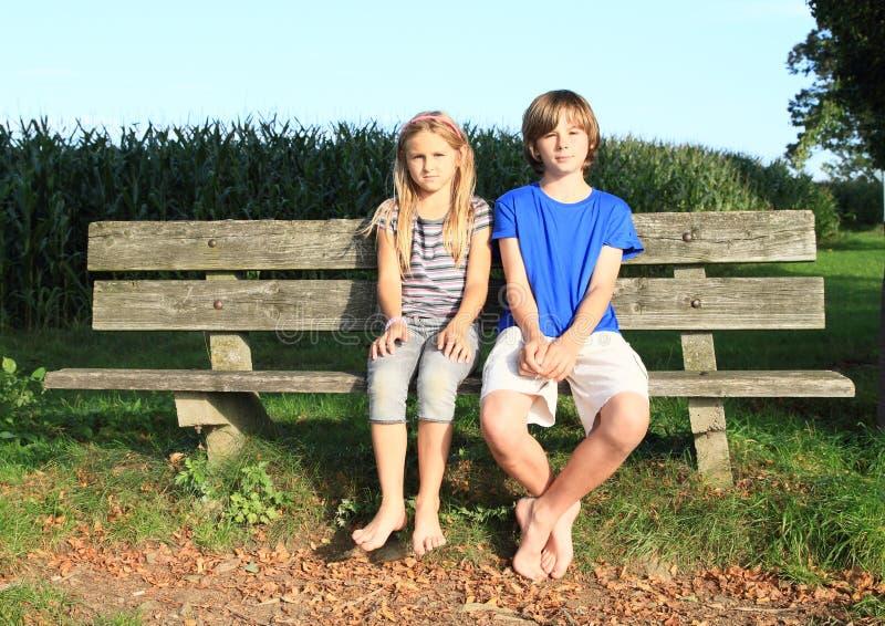 Małe dzieci - dziewczyny i chłopiec obsiadanie na ławce obrazy royalty free