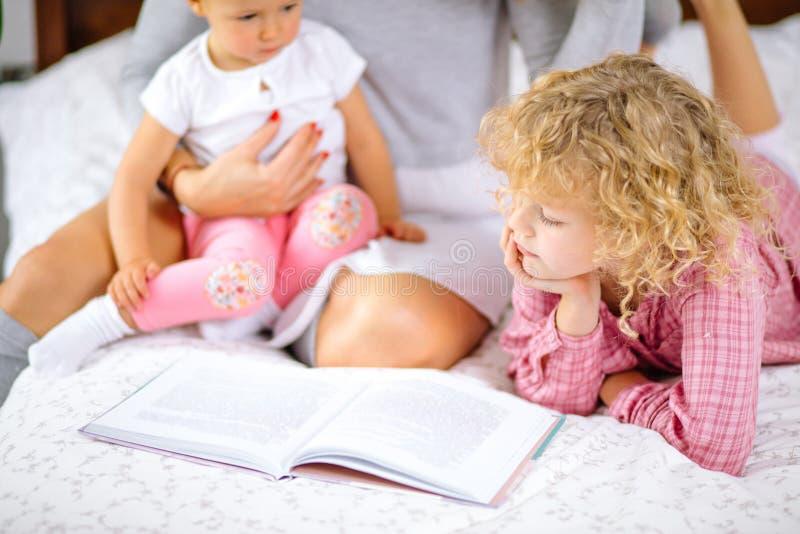 Małe dzieci patrzeje przez książki podczas gdy siedzący na łóżku z matką obraz royalty free