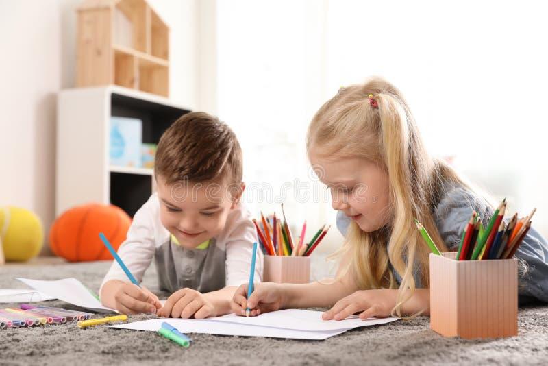 Małe dzieci rysuje indoors zdjęcia stock