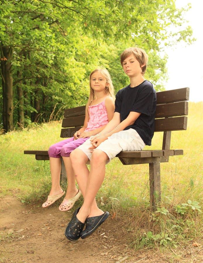 Małe dzieci siedzi na ławce obraz stock