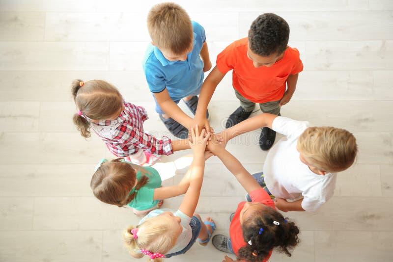 Małe dzieci stawia ich ręki wpólnie indoors fotografia stock