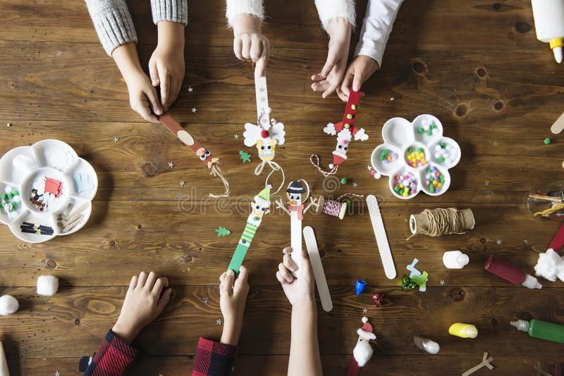 Małe dzieci trzyma Bożenarodzeniowy charakter dekorujących popsicle kije fotografia royalty free