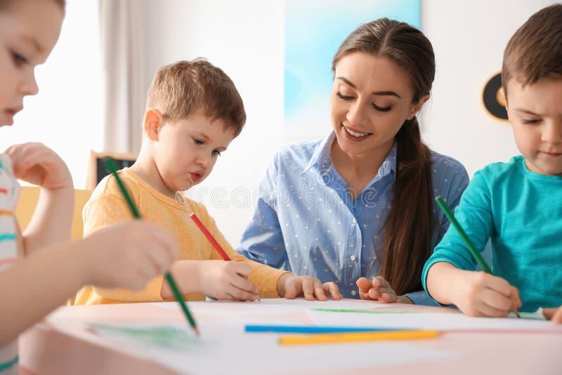 Małe dzieci z dziecina nauczyciela rysunkiem przy stołem indoors fotografia stock