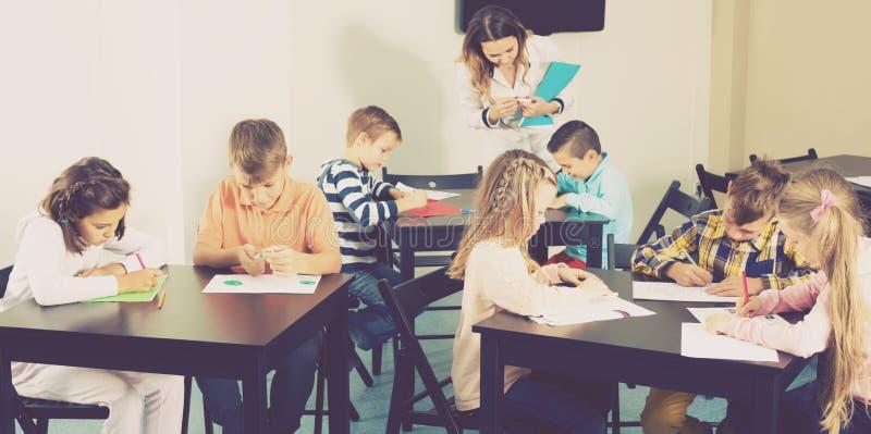 Małe dzieci z fachowym nauczyciela rysunkiem w sala lekcyjnej zdjęcia royalty free
