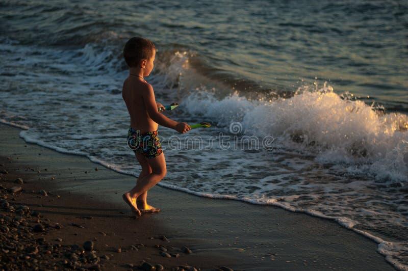 Małe dziecko bawić się z wodą fala Plaża zdjęcie stock