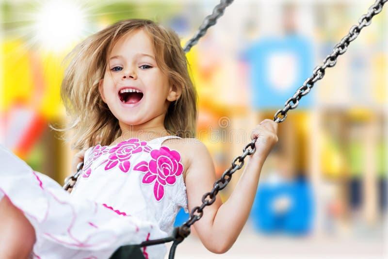 Małe dziecko blond dziewczyna ma zabawę na huśtawce fotografia royalty free