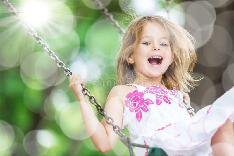 Małe dziecko blond dziewczyna ma zabawę na huśtawce obrazy royalty free