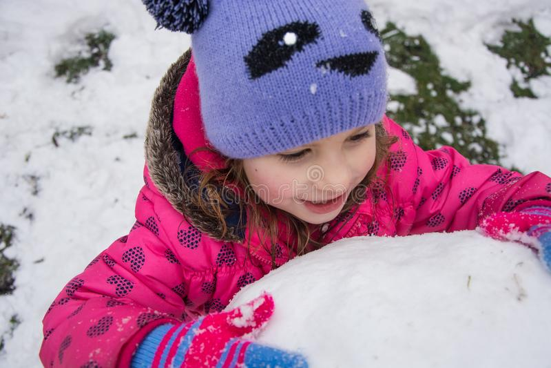 Małe dziecko buduje ogromnego snowball dla bałwanu fotografia royalty free