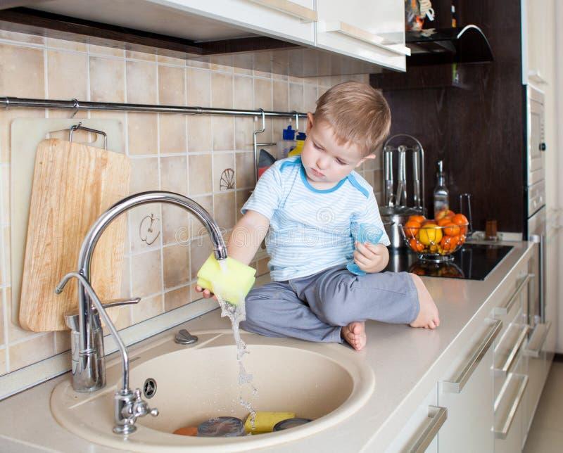 Małe dziecko chłopiec domycia naczynie na kuchni obraz stock