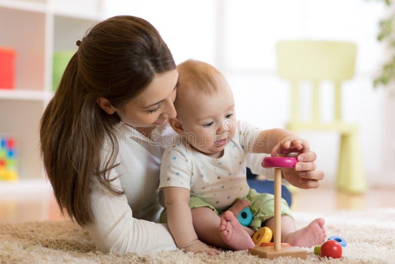 Małe dziecko chłopiec i jego mamusie bawić się z zabawkami w domu zdjęcie royalty free