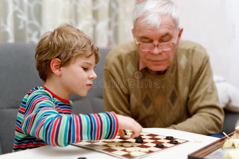 Małe dziecko chłopiec i seniora dziad bawić się wpólnie warcabów gemowych zdjęcia royalty free