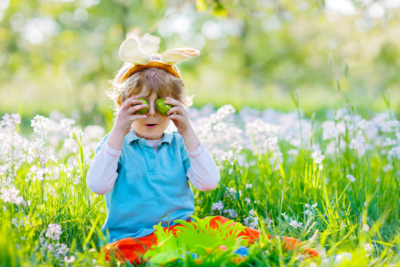 Małe dziecko chłopiec ma zabawę z tradycyjnym Wielkanocnego jajka polowaniem obraz stock