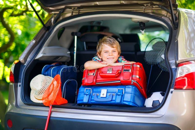 Małe dziecko chłopiec obsiadanie w samochodowym bagażniku tuż przed opuszczać dla vaca obraz royalty free