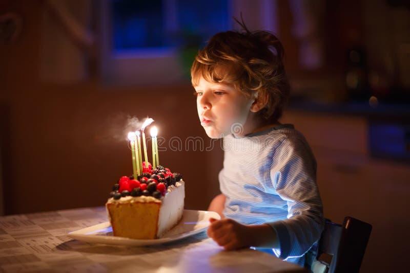 Małe dziecko chłopiec podmuchowe świeczki na urodzinowym torcie fotografia stock