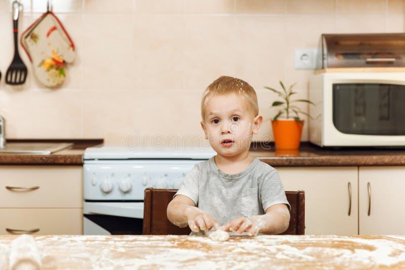Małe dziecko chłopiec pomocy matka gotować imbirowego ciastko Szczęśliwa rodzinna mama i dziecko w weekendowym ranku w domu związ fotografia stock