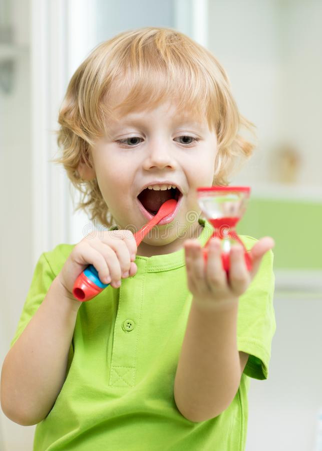 Małe dziecko chłopiec szczotkuje jego zęby i patrzeje hourglass obrazy royalty free