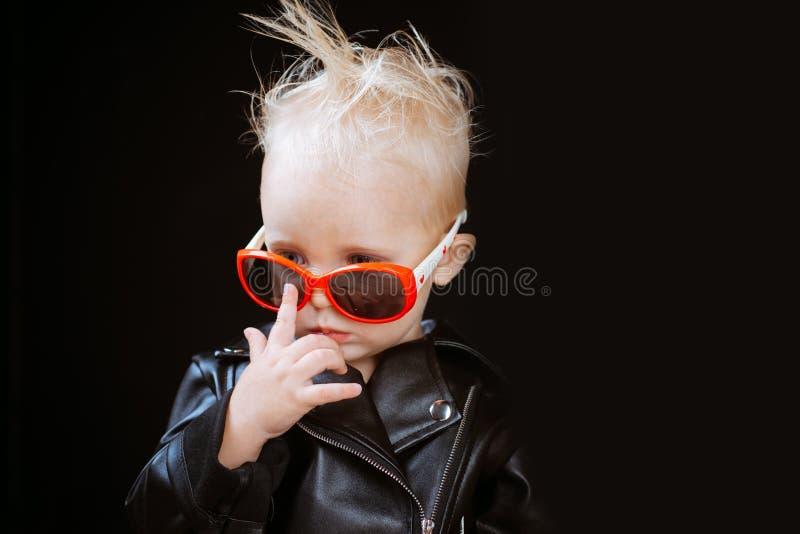 Małe dziecko chłopiec w bujaków okularach przeciwsłonecznych i kurtce Rockowy stylowy dziecko  obraz royalty free