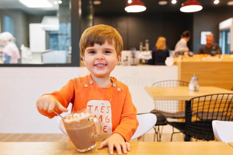 Małe dziecko chłopiec w pomarańczowym pulowerze ma zabawę z filiżanką udział czekolada w kawiarni Jest u?miechni?ty kamera obrazy royalty free