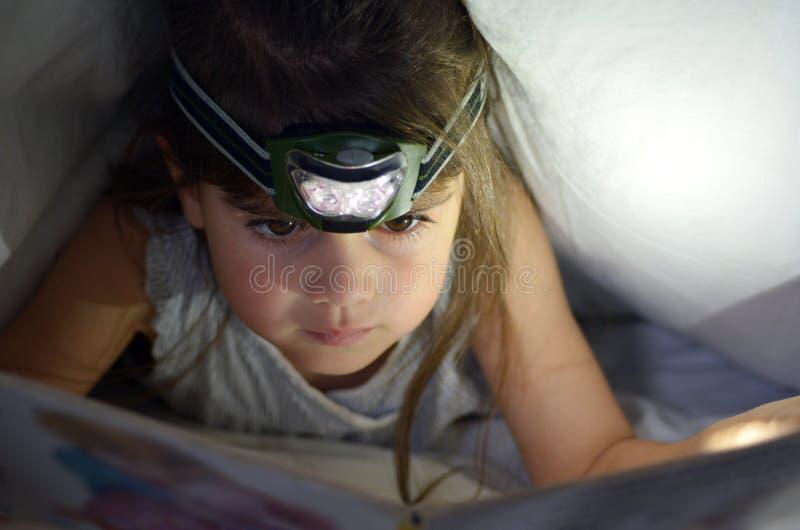 Małe dziecko czyta książkę w łóżku pod pokrywami przy nocą zdjęcia stock