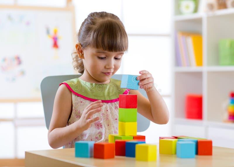 Małe dziecko dziewczyna bawić się z drewnianymi kolorowymi sześcianami w pepiniera dziecinu lub pokoju zdjęcie royalty free