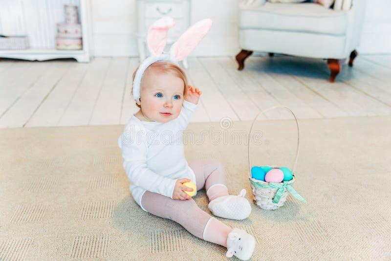 Małe dziecko dziewczyna jest ubranym królików ucho na Wielkanocnym dniu i bawić się z malującymi jajkami obraz royalty free