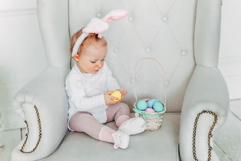 Małe dziecko dziewczyna jest ubranym królików ucho na Wielkanocnym dniu i bawić się z malującymi jajkami obraz stock