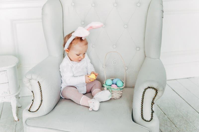 Małe dziecko dziewczyna jest ubranym królików ucho na Wielkanocnym dniu i bawić się z malującymi jajkami obrazy stock
