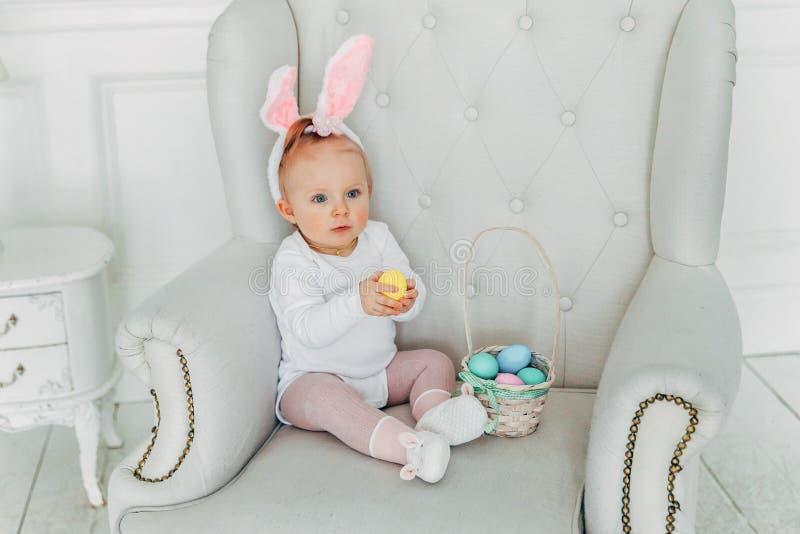 Małe dziecko dziewczyna jest ubranym królików ucho na Wielkanocnym dniu i bawić się z malującymi jajkami zdjęcia royalty free