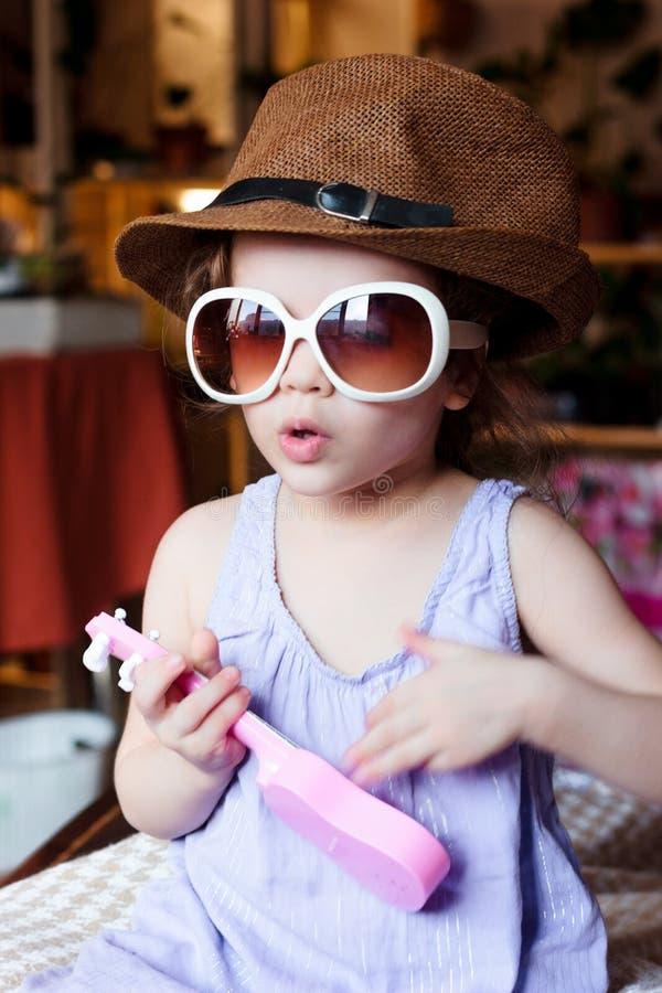Małe dziecko dziewczyna ma zabawę z zabawkarską gitarą w rękach i okularach przeciwsłonecznych na twarzy obrazy stock