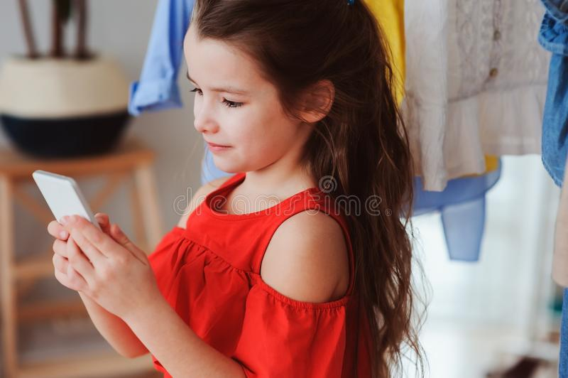 małe dziecko dziewczyna robi selfie podczas gdy próbujący na nowym odziewa w jej garderoby lub sklepu trafnym pokoju obraz stock