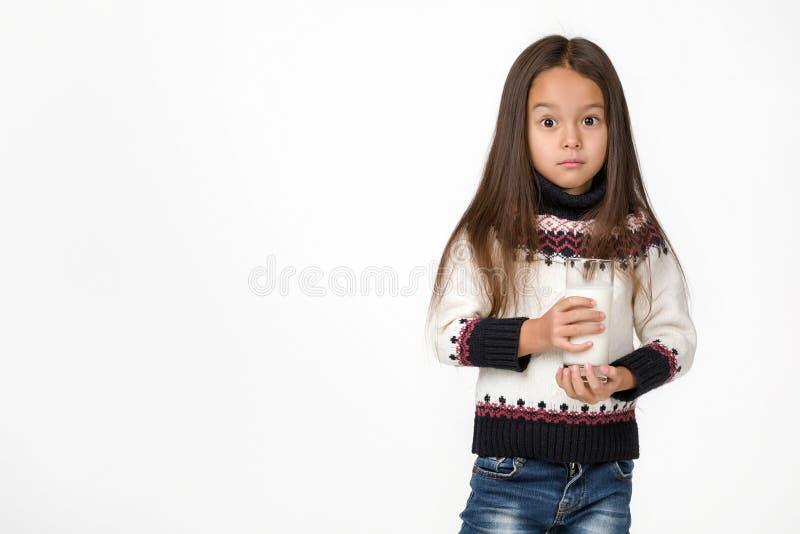 Małe dziecko dziewczyna trzyma szkło mleko na białym tle zdjęcie stock