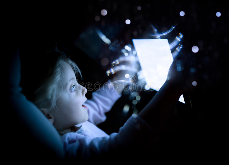 Małe dziecko dziewczyna używa pastylki technologię w łóżku nocą w domu zdziwiona dzieciak córka w sypialni dopatrywania filmu lub obrazy royalty free