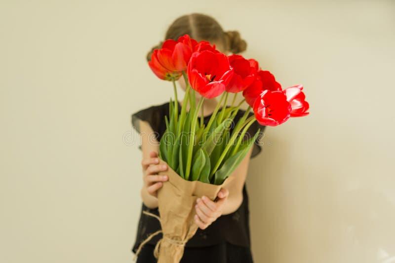Małe dziecko dziewczyny mienia bukiet czerwoni tulipany zdjęcia stock