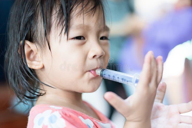 Małe dziecko ono karmi z wodą w strzykawce obraz royalty free