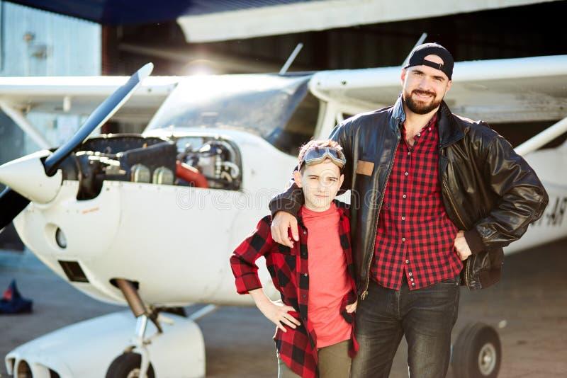 Małe dziecko przychodził jego ojca miejsce pracy przy samolotu hangaru budynkiem zdjęcie royalty free